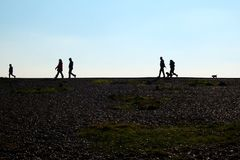 A pebble beach and unrecognisable people walking on the horizon royalty free stock image
