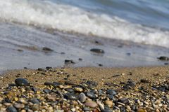 Pebble beach waves. Waves breaking on sand and pebble beach Stock Image