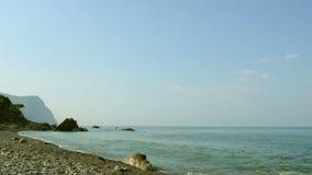 Pebble beach, waves, rocks and mountain stock footage