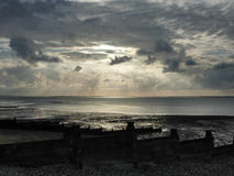 Pebble Beach at Whitstable with jacobs ladder sunlight Royalty Free Stock Images