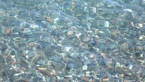 Pebble bottom under clear shallow water surface 4K shot stock video footage