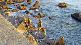 Pebble castles. Child locks of pebbles on the shore of the Black Sea Stock Photos
