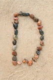 Pebble d letter  on sand Stock Photos