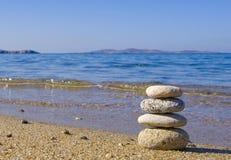 Pebble heap on the sand near the sea Royalty Free Stock Photo