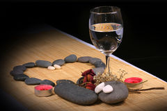 Pebble Heart, Glass, and dried flowers on the rattan background Stock Photos