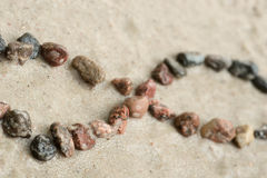 Pebble infinity symbol on sand selective focus. Pebble infinity symbol on sand background selective focus stock photography
