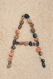 Pebble  a letter on sand Royalty Free Stock Photos