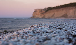 Pebble limestone beach during sunset Stock Photography