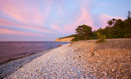 Pebble limestone beach during sunset Stock Images