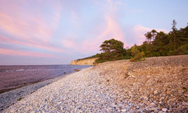 Pebble limestone beach during sunset Royalty Free Stock Photos