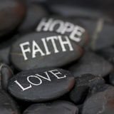 Pebble with message. Black pebble with engraved message love, faith, hope royalty free stock images