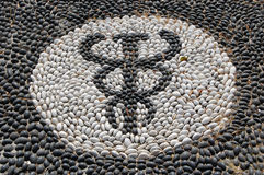 Pebble mosaic of the symbol of Hypocrates. Known as one of the worlds first docotors royalty free stock photo