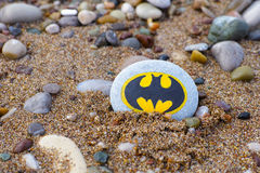 Pebble with painted sign Batman on beach. Paphos, Cyprus - November 22, 2016 Pebble with painted sign Batman lying on the beach with sand and stones stock photography