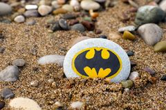 Pebble with painted sign Batman on beach with sand and pebbles. Paphos, Cyprus - November 22, 2016 Pebble with painted sign Batman on beach with sand and pebbles royalty free stock photography