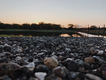 Pebble perspective. Artsy perspective on pebbles around a lake with a dock and sunset in the background royalty free stock photo