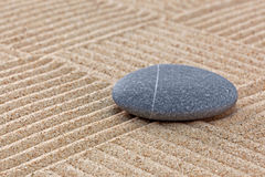 Pebble on raked sand squares. A pebble on a raked sand zen garden with patchwork patterns Royalty Free Stock Photo