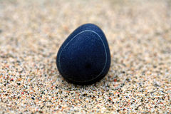 Pebble in sand Stock Image