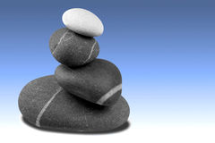 Pebble sculpture on blue. Stock Photos