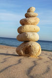 Pebble stack on sandy beach Stock Image
