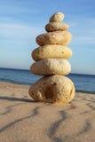 Pebble stack on sandy beach Stock Image