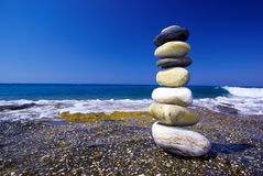 Pebble stack and sea waves. On the background Royalty Free Stock Photo