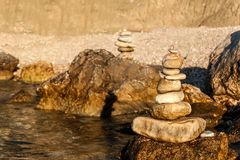 Pebble stack on the seashore. Pyramid of stones on the beach. Light at sunset. Symbol of patience. Concept of harmony and balance. Pebble stack on the seashore stock photography