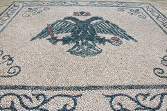 Pebble stone floor with a picture of double eagle, Rhodes. Stock Photos