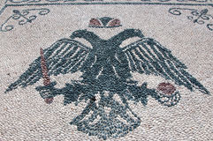 Pebble stone floor with a picture of double eagle, Rhodes. Royalty Free Stock Photos