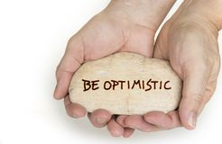 Pebble stone in hands. Concept for a be optimistic sign stock images