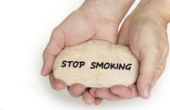 Pebble stone in hands. Concept for a stop smoking sign stock photography
