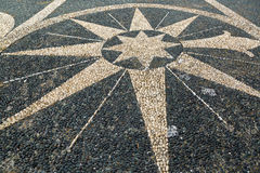 Pebble stone mosaic arranged in a symbol on pavement pedestrian Royalty Free Stock Photography