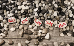 Pebble stones with german text for luck, force, fun, love and po Royalty Free Stock Photo
