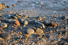 Pebble stones near the sea in bright sunset light Stock Photo