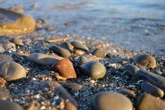 Pebble stones near the sea in bright sunset light Stock Image