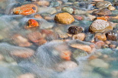 Pebble stones in the river water close up view Stock Images