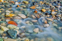 Pebble stones in the river water close up view. Natural background Royalty Free Stock Photo