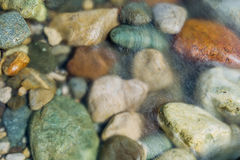 Pebble stones in the river water close up view Royalty Free Stock Photo