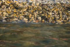 Pebble stones on the sea beach, the rolling waves of the sea with foam Stock Photo