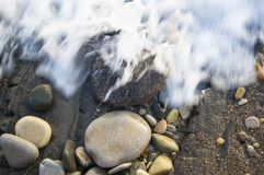 Pebble stones on the sea beach, the rolling waves of the sea with foam Royalty Free Stock Photo