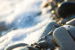 Pebble stones on the sea beach, the rolling waves of the sea with foam Royalty Free Stock Image