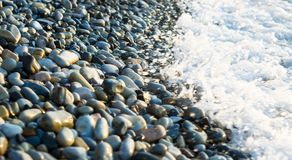 Pebble stones on the sea beach, the rolling waves of the sea with foam Stock Photos