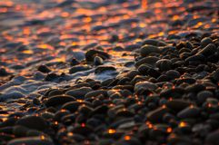 Pebble stones on the sea beach, the rolling waves of the sea with foam Royalty Free Stock Photos