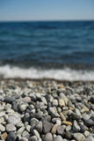 Pebble stones and with tidal bore of sea on background Royalty Free Stock Images