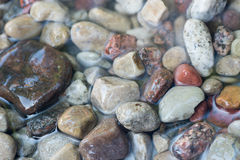 Pebble stones in water background Stock Photos