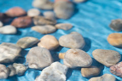 Pebble stones in water. Closeup Royalty Free Stock Images