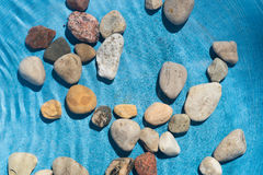 Pebble stones in water. Closeup Royalty Free Stock Photography