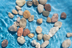 Pebble stones in water. Closeup Stock Images