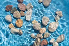 Pebble stones in water. Closeup Royalty Free Stock Image