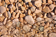 Pebble stones in water in the sun. Pebble stones in water shining in the sun Royalty Free Stock Photo