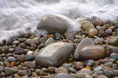 Pebble stones and wave Stock Photos